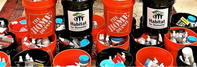 Stacked containers labelled with Home Depot and Habitat for Humanity.